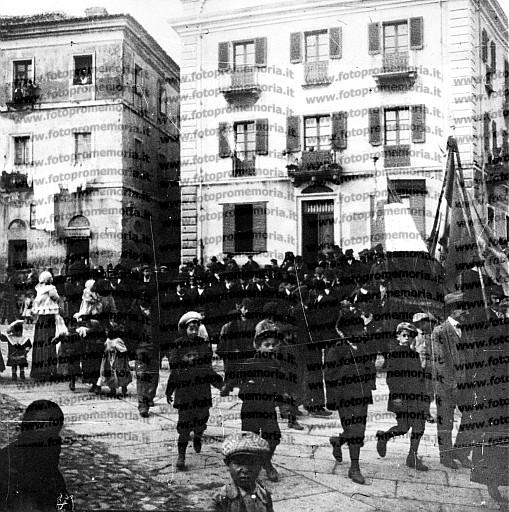 Nuoro, 1911. I lavoratori della Società Operaia, seguiti dalle loro famiglie, sfilano in corteo per le vie della città.