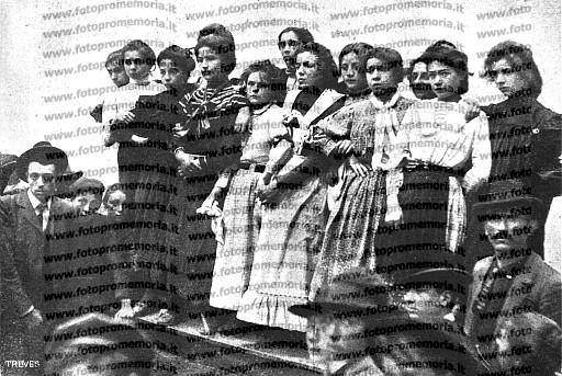 Milano, 1902. Un gruppo di giovani operaie, apprendiste nei laboratori di sartoria e modisteria, che hanno aderito allo sciopero delle 'piscinine'.