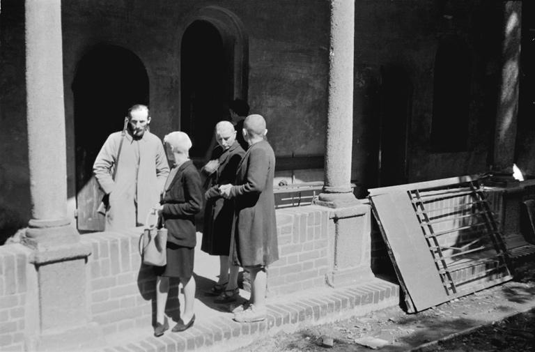 Via San Gregorio, nel chiostro del Lazzaretto, tre donne accusate di collaborazionismo rasate a zero e sorvegliate da un partigiano armato di moschetto.