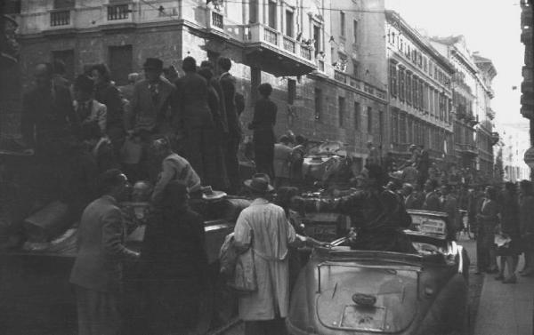 Corso Monforte nei pressi del Palazzo del Governo sede della Prefettura, colonna di carri armati Sherman dell'esercito americano sommersi dalla folla in festa